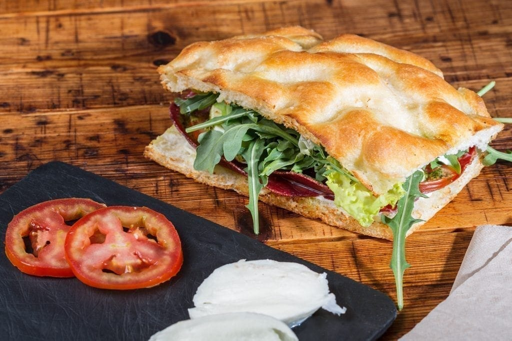 Sandwich Giuseppito en pan focaccia con bresaola, pesto casero, mascarpone, mozzarella de búfala, tomate y rúcula.